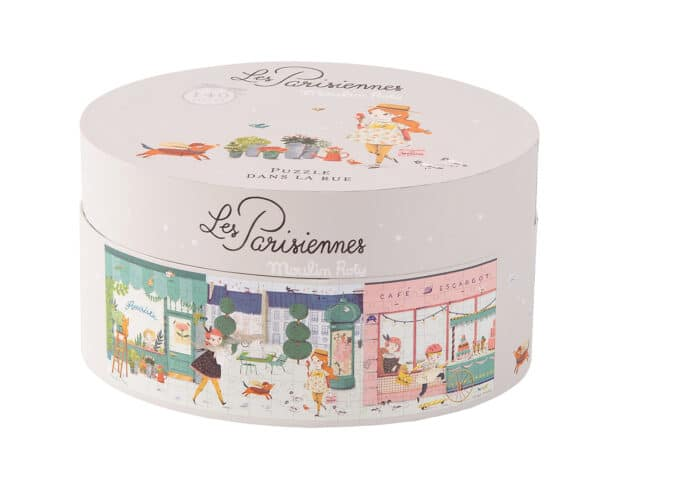 Cylinder shaped box of Les Parisiennes puzzle dans la rue, the box is decorated with an illustration of the puzzle and other motifs - Moulin Roty 642 541